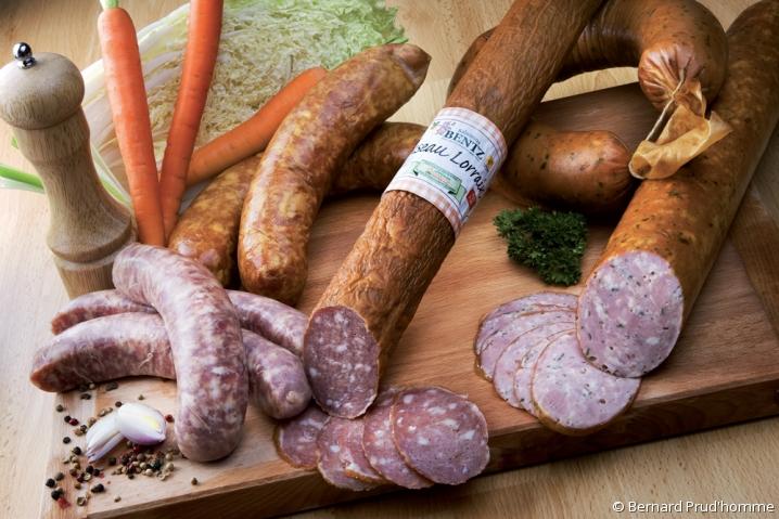 Sélection de charcuterie de la maison Bentz : saucisse fumée entourée de carottes et pommes de terre.