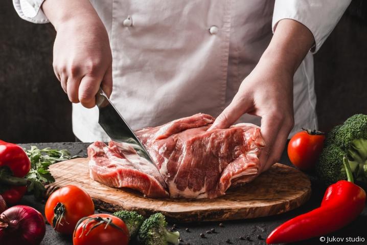 Artisan boucher tranchant un bifteck