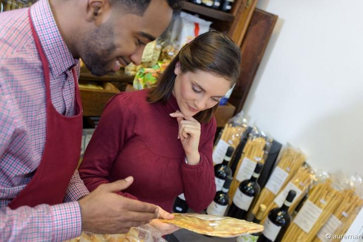 Commerçant conseillant une cliente sur des produits bio, dans une boutique alimentaire