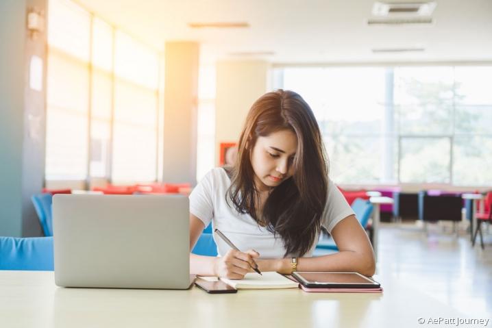Jeune fille révisant ses cours grâce à une tablette numérique