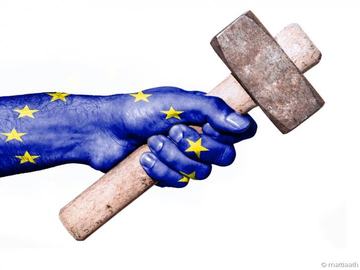 Drapeau européen en filigrane d'une main tenant un marteau