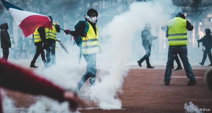 Manifestant gilet jaune brandissant un drapeau français au milieu des fumigènes