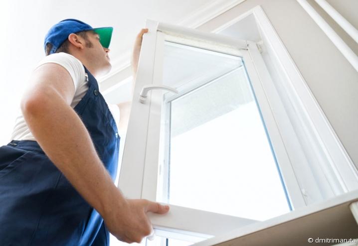 Artisan réalisant des travaux d'isolation sur une fenêtre