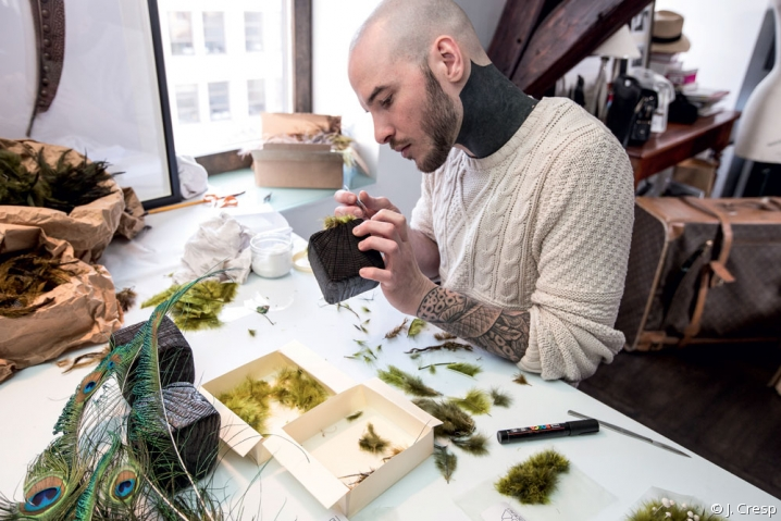 Le plumassier Maxime Leroy assis derrière son établis, en plein collage de plumes vertes