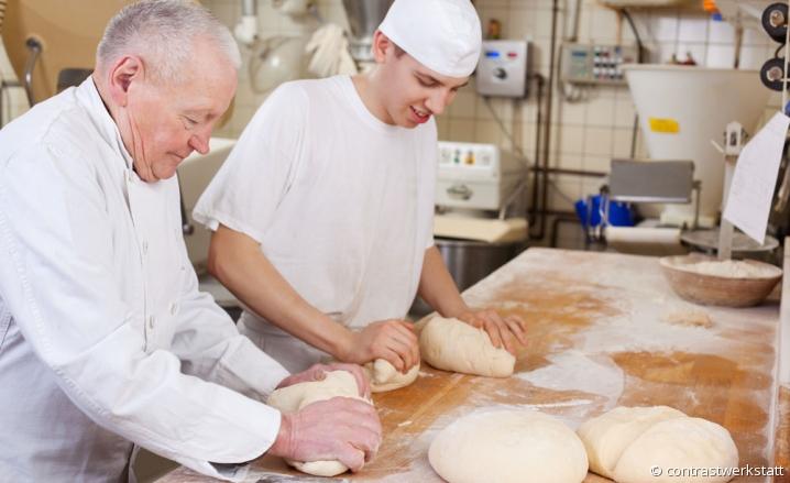 Artisan boulanger pétrissant des pâtons aux côtés de son apprenti