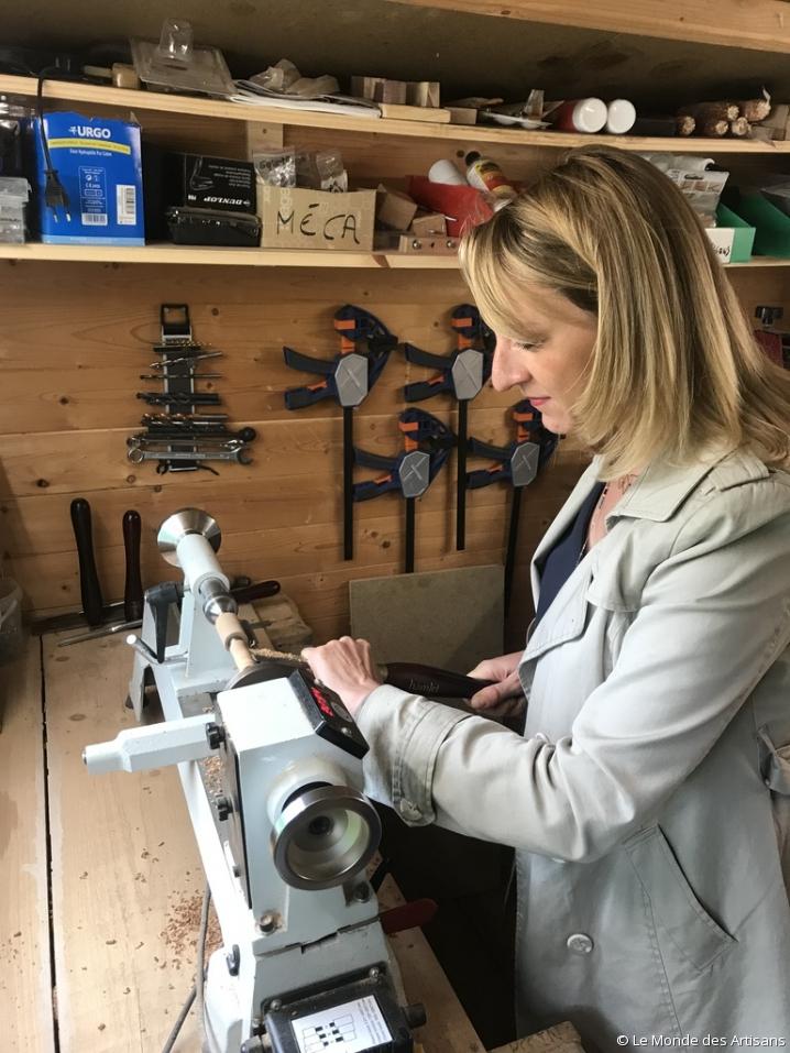 Vêtue d'une blouse blanche, la journaliste Julie Clessienne s'essaie au tour de bois