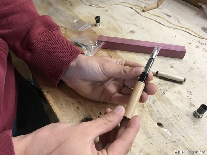 Le stylotier tient le produit fini : un stylo en bois tourné
