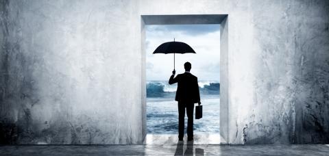 Employé sur le départ franchissant le seuil d'une porte, face à une mer agitée