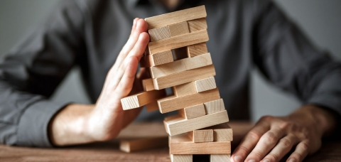Illustration d'une entreprise fragile : jeu d'équilibre avec des pièces de bois