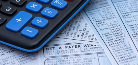 vue d'une calculatrice posée sur des fiches de paie