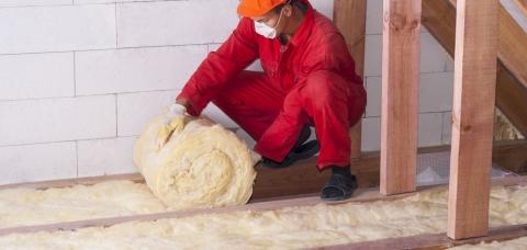 Artisan posant de la laine de verre au sol pour isoler des combles