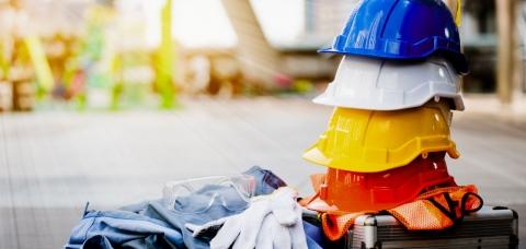 Pile de casques de chantier, symbole de la pénurie de main-d'oeuvre.