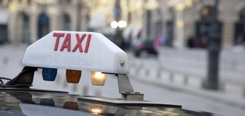 """Gros plan sur le panneau blanc lumineux """"taxi"""" qui surmonte les voitures à Paris"""