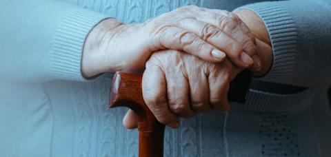 Mains de femme âgée tenant le pommeau d'une canne